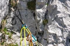 Den Einstieg haben wir schon ein bisschen gesucht...Die im Topo verzeichnete Gufel hab ich nicht gesehen aber der Kamin ist der Hinweis. Hier kein Haken! Wir haben im Aufstiegssinn wenige Meter links unterhalb des Starts eine grüne Sanduhrschlinge hinterlassen (um uns den Schrofenwackler zu sparen...).